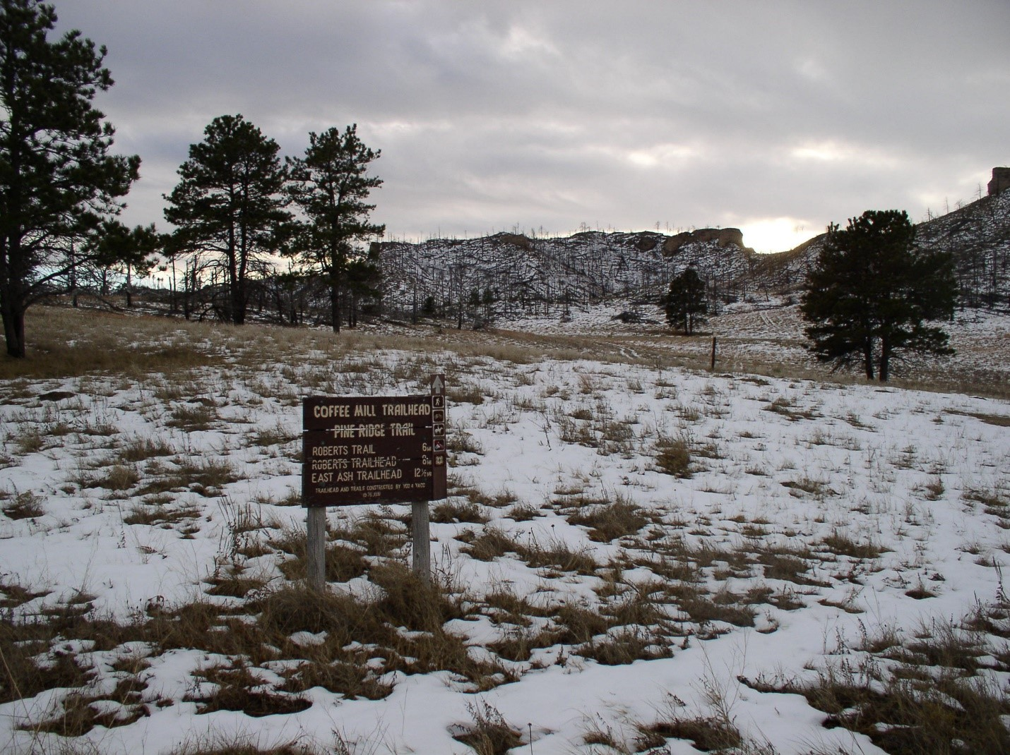 Coffee Mill Trailhead sign in open space with a light dusting of snow