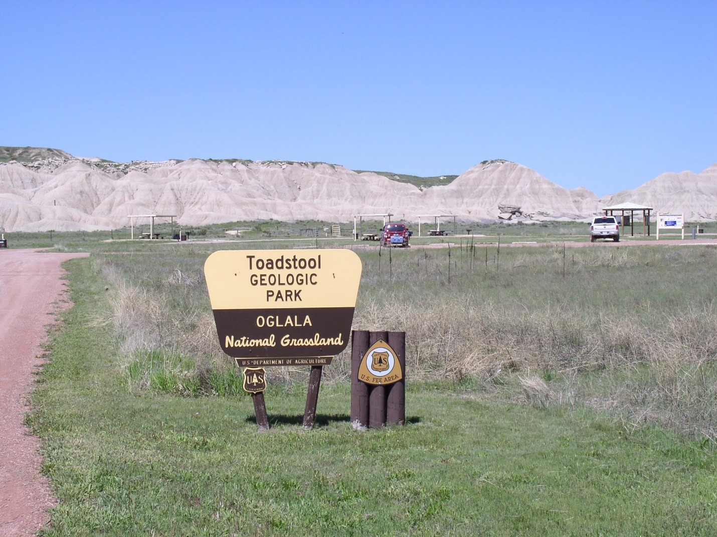 Toadstool Geologic Park sign with sites in the background