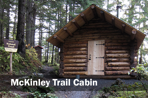 The front of McKinley Trail cabin with the signpost off to the left