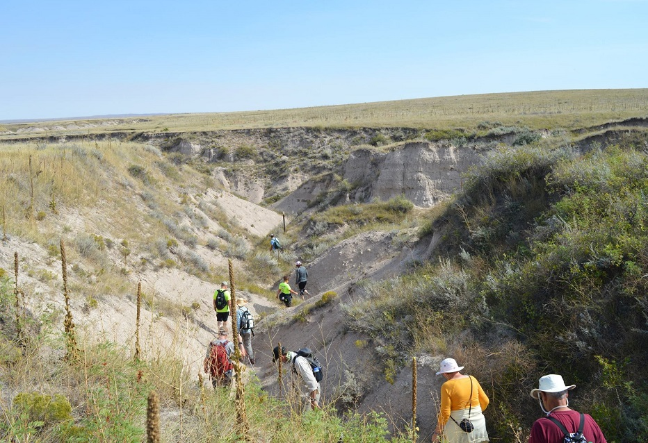 People hike on a sunny day at Great Plains Trail segment at Toadstool Geological Park