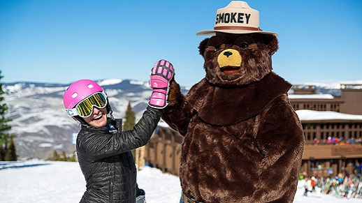 Smokey Bear and a skier give each other a hi-five.