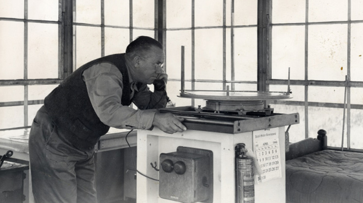 Interior of Mikes Knob Tower showing lookout Charles Dobson using his Osborne Fire Finder to spot a smoke in April 1946