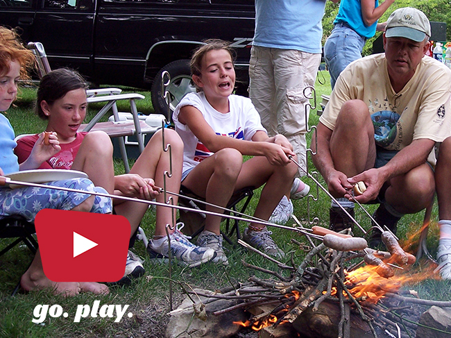 A family gathers around a campfire to roast sausages. Text over the image says Go Play.