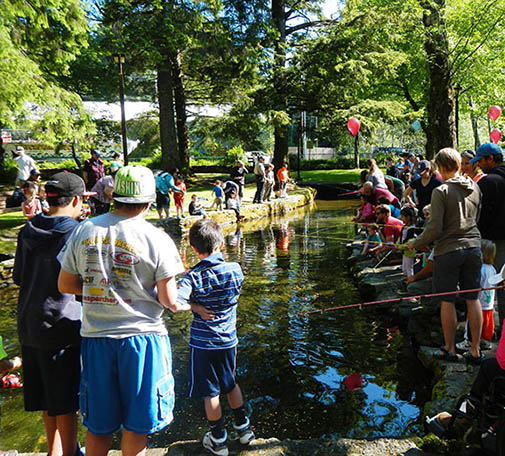 Kids enjoying fishing at city park in Ketchikan, Alaska. Creek and trees surrounding the area