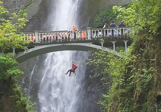 A person hangs off belay in front of Multnomah Falls.