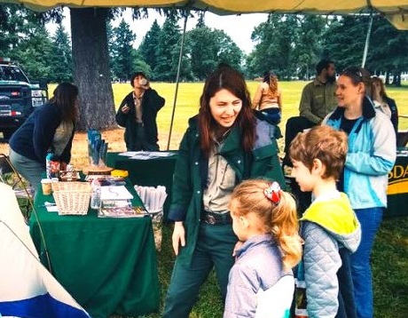 Rangers talk woth kids about the outdoors at an event.