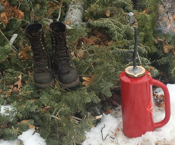 firefighter boots and drip torch container on green needles and snow