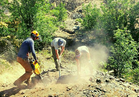 Three workers dig into a dusty trail with tools.