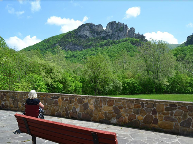 A woman sits at an observation area looking a Seneca Rocks