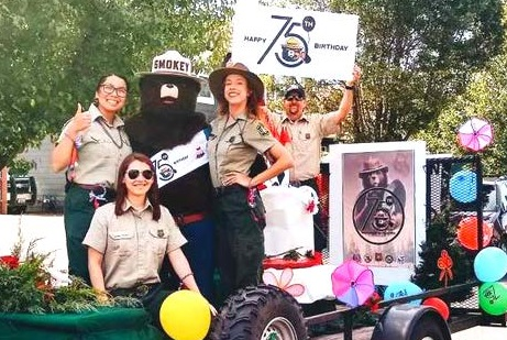 Forest Service employees gather on a float with Smokey Bear