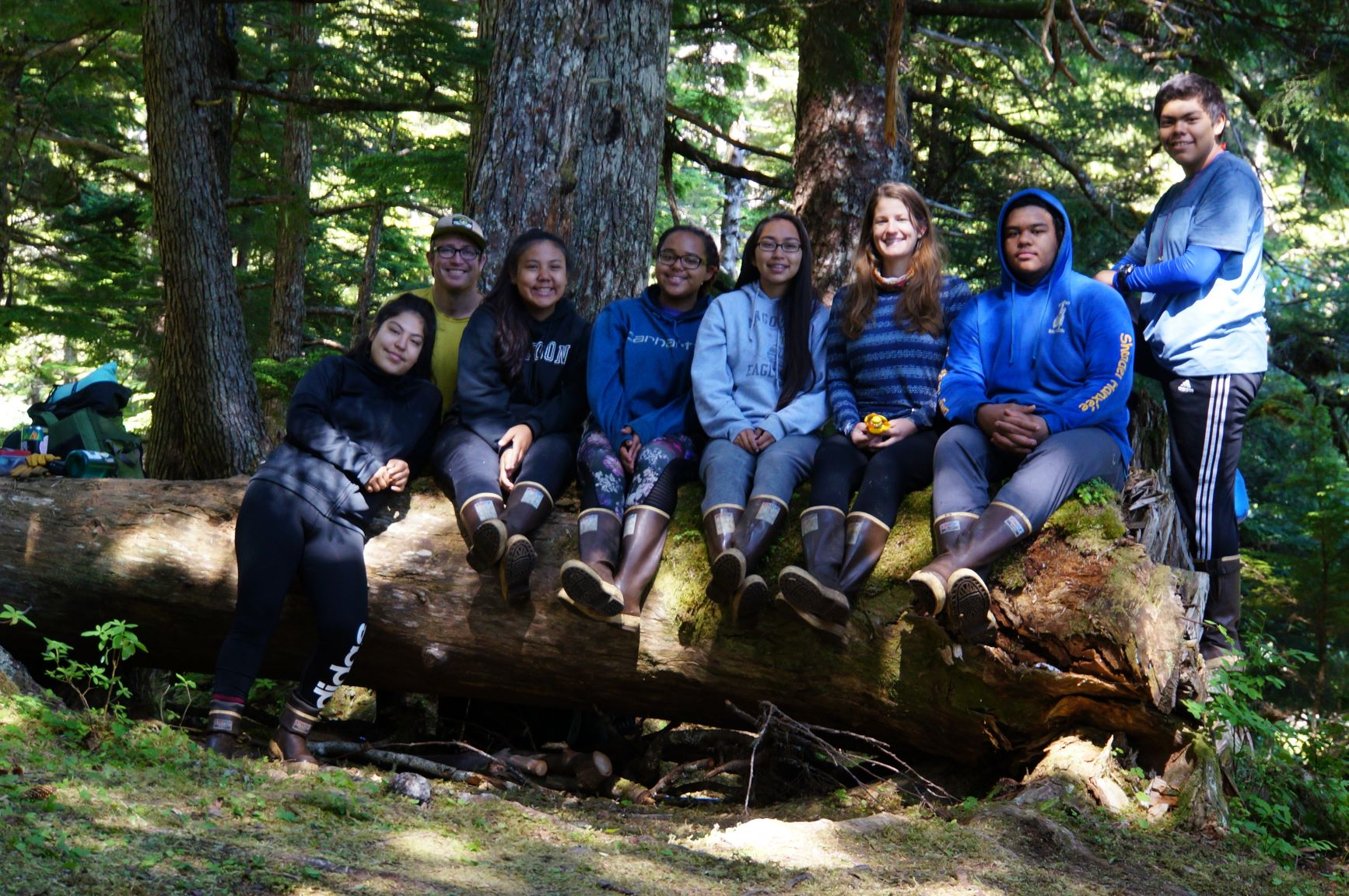 Angoon YCC crew poses on a log, forest in the background