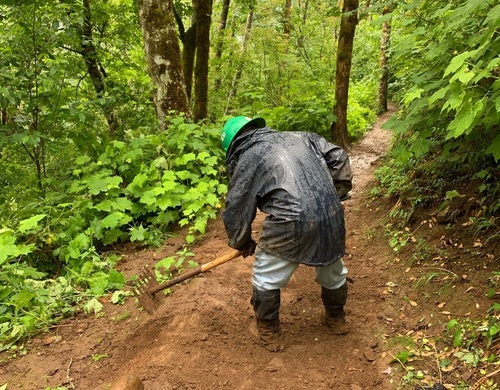 A person in rain gear labors on a trail