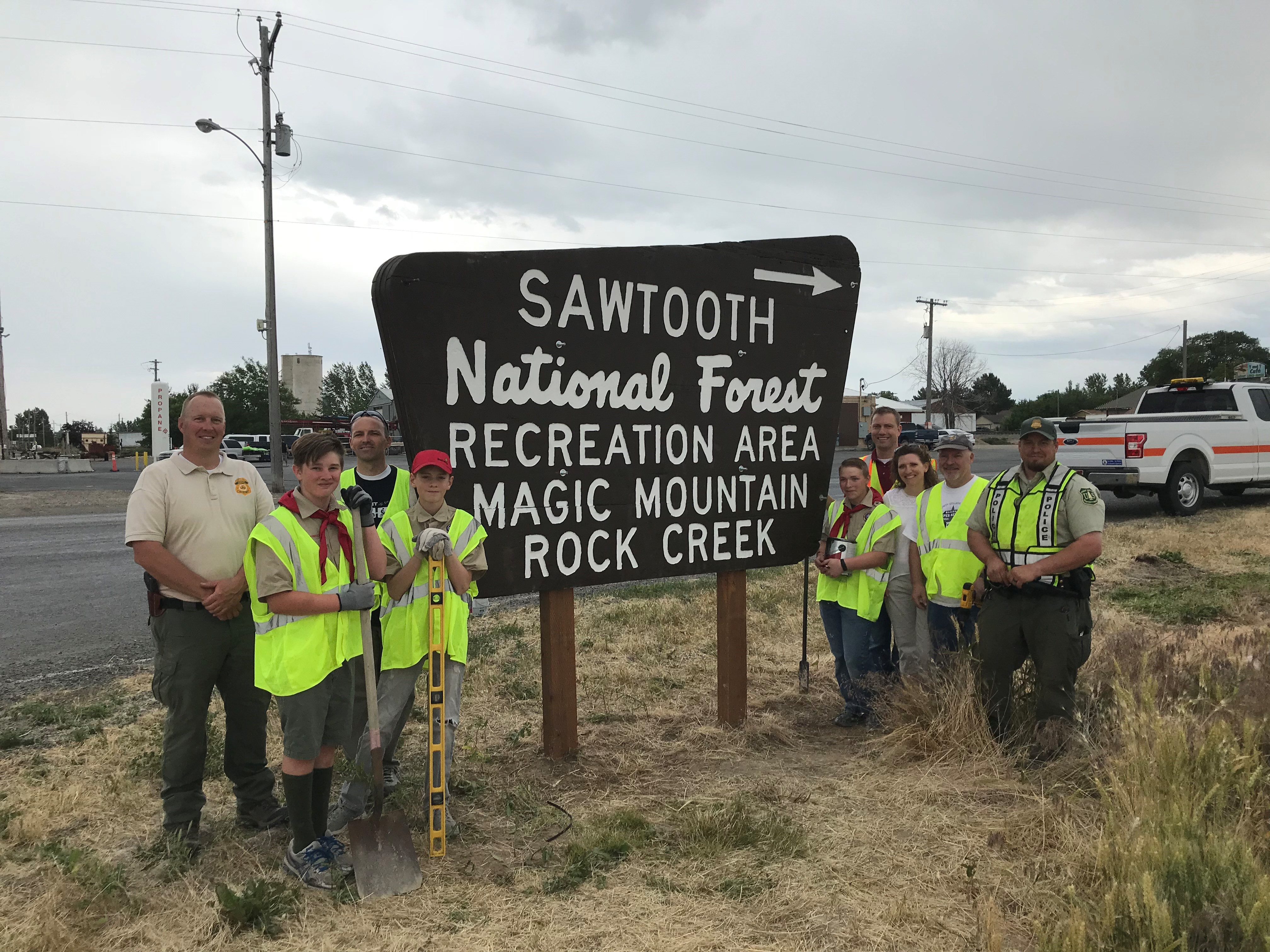 A group of adults and boy scouts standing next to a forest sign. One boy scout is holding a shovel.