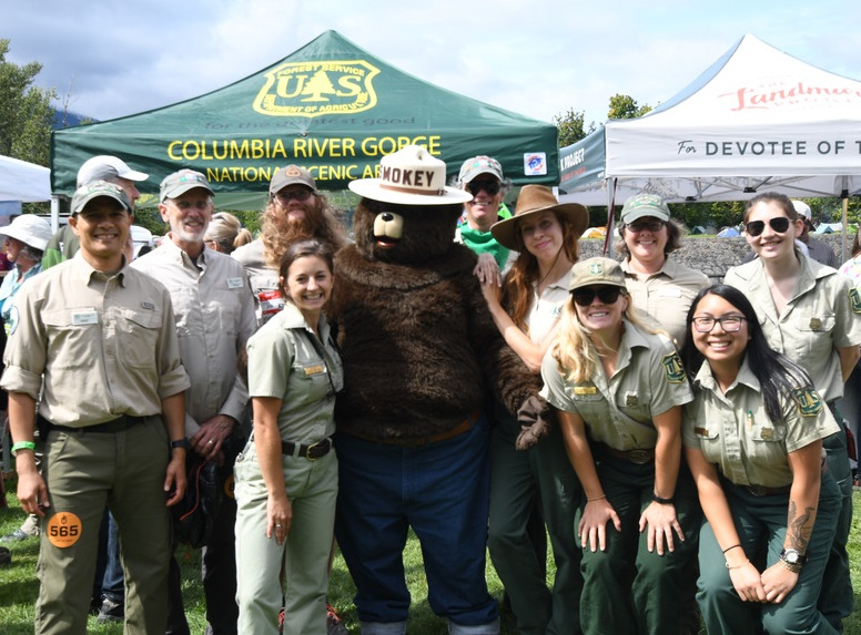 Rangers in uniform pose with Smokey Bear at a public event.