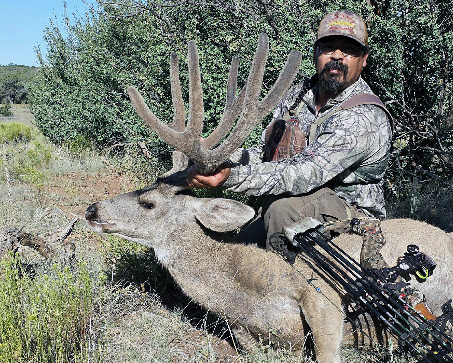 Archery hunter with his bow and arrows and recent Elk kill on ground in the forest