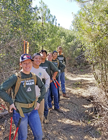 A group of teenage boys and girls stand on a trail they just brushed and maintained.