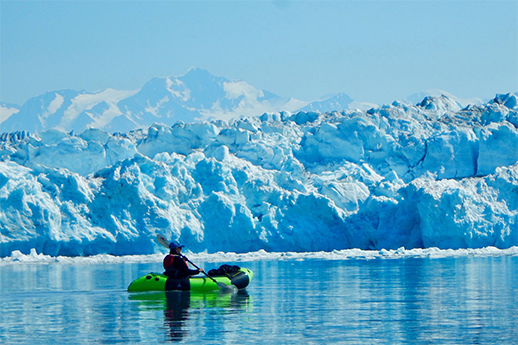 A tiny raft in front of a massive wall of glacial ice.
