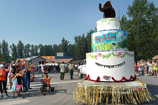 Smokey bear on top of a parade float in the shape of a multi-tiered birthday cake.
