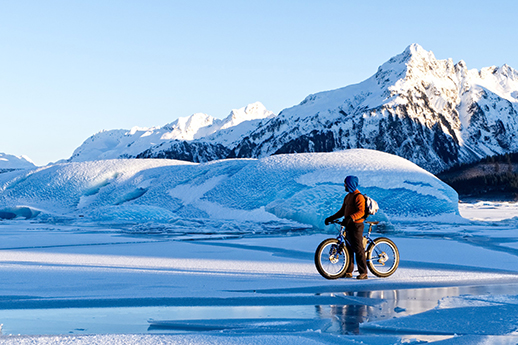 A biker riding across a frozen lake on a lovely day.