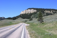 Image of a road stretching across a landscape towards some buttes