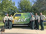Forest Service law enforcement officers stand in front of decal-painted D.A.R.E. vehicle.