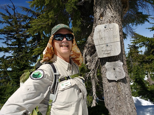 Wilderness steward stands next to a trail sign smiling on a snowy slope .