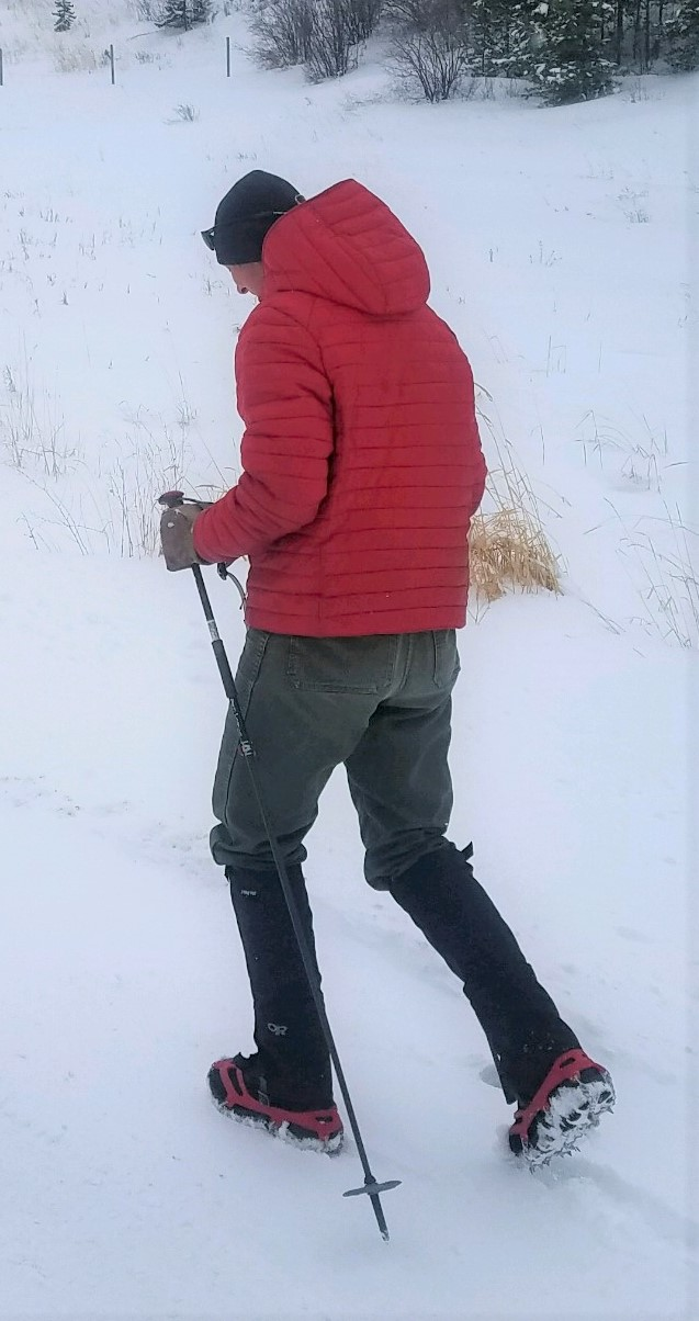 Hiker with poles and traction devices in snow.