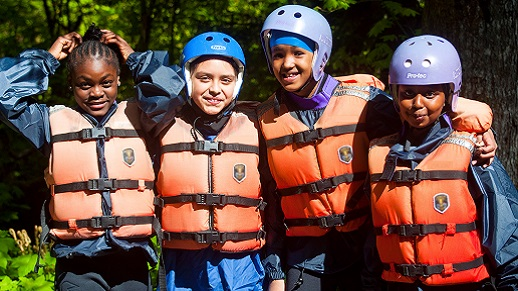 Four girls in life jackets and helmets pose for the camera smiling.