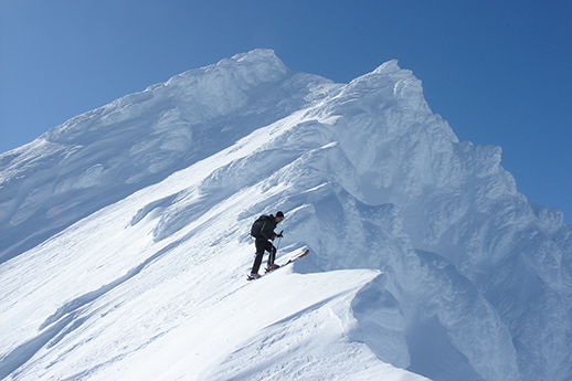 A skier poised at the top of a snowy mountain