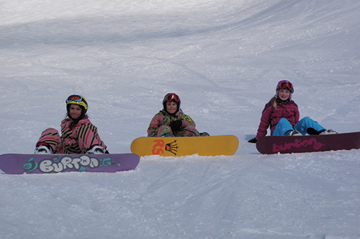 Three young snowboarders sitting on the slope.