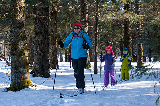 A woman leads two youngsters on a forest ski trail in Portage Valley.