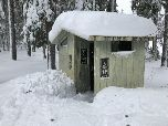 Snow covered vault toilet.