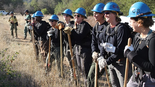 photograph of women dressed in field safety gear standing in a line with tools and blue helmets
