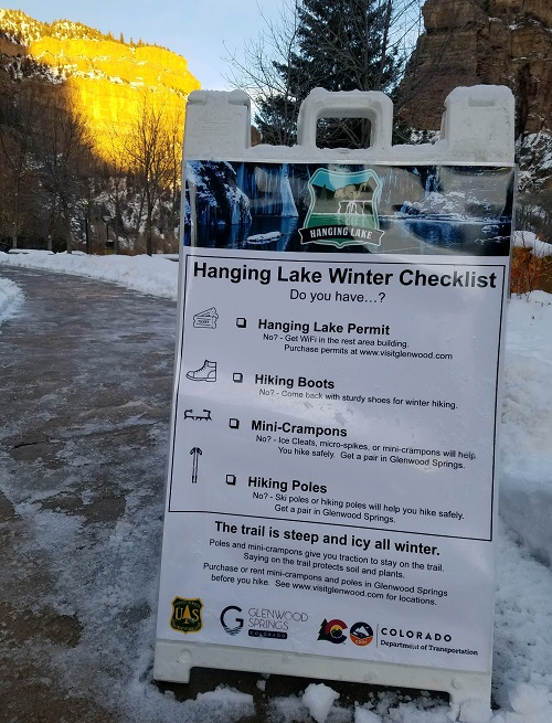 A snowy path and a large sandwich board reminder of things visitors need in winter at Hanging Lake