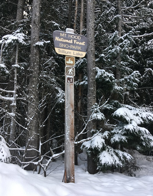 A sign for Trillium Sno Park with a back-drop of snow covered trees.