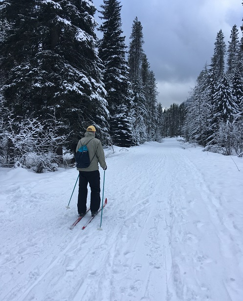 A man skis on a wide cross country ski snow trail