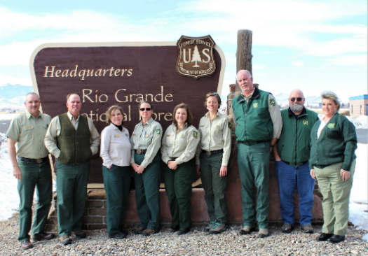 Members of the leadership team stand in front of the Rio Grande National Forest Headquarters sign