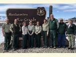 Leadership team members stand in front of Rio Grande National Forest Headquarters sign