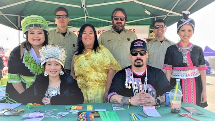 Forest Service employees pose with Hmong wearing traditional dress.