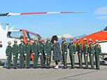 Men and women from the Forest Service are in dress uniforms standing at attention with helicopters.
