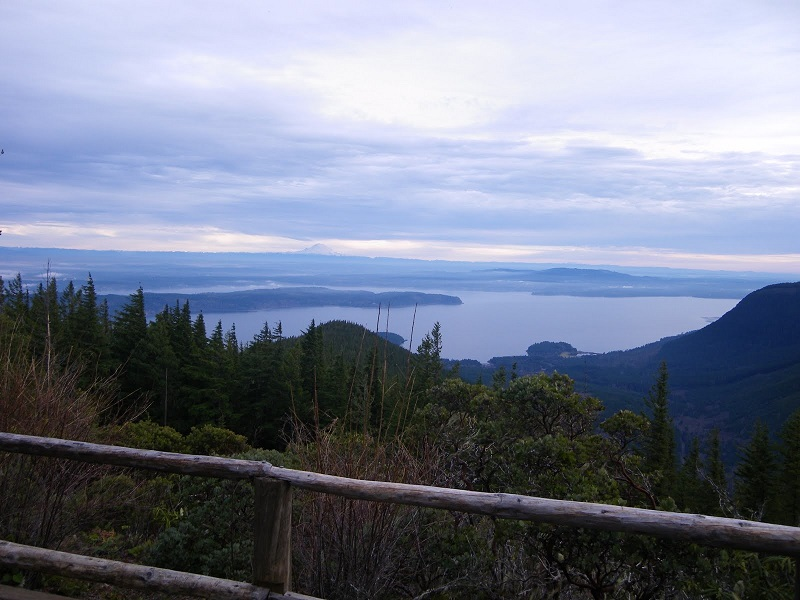 Looking out at the clouds below over the large blue water of the  Hood Canal