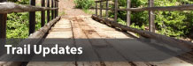 Photo of a wooden bridge on a trail in the woods with the text Trail Updates overlaid