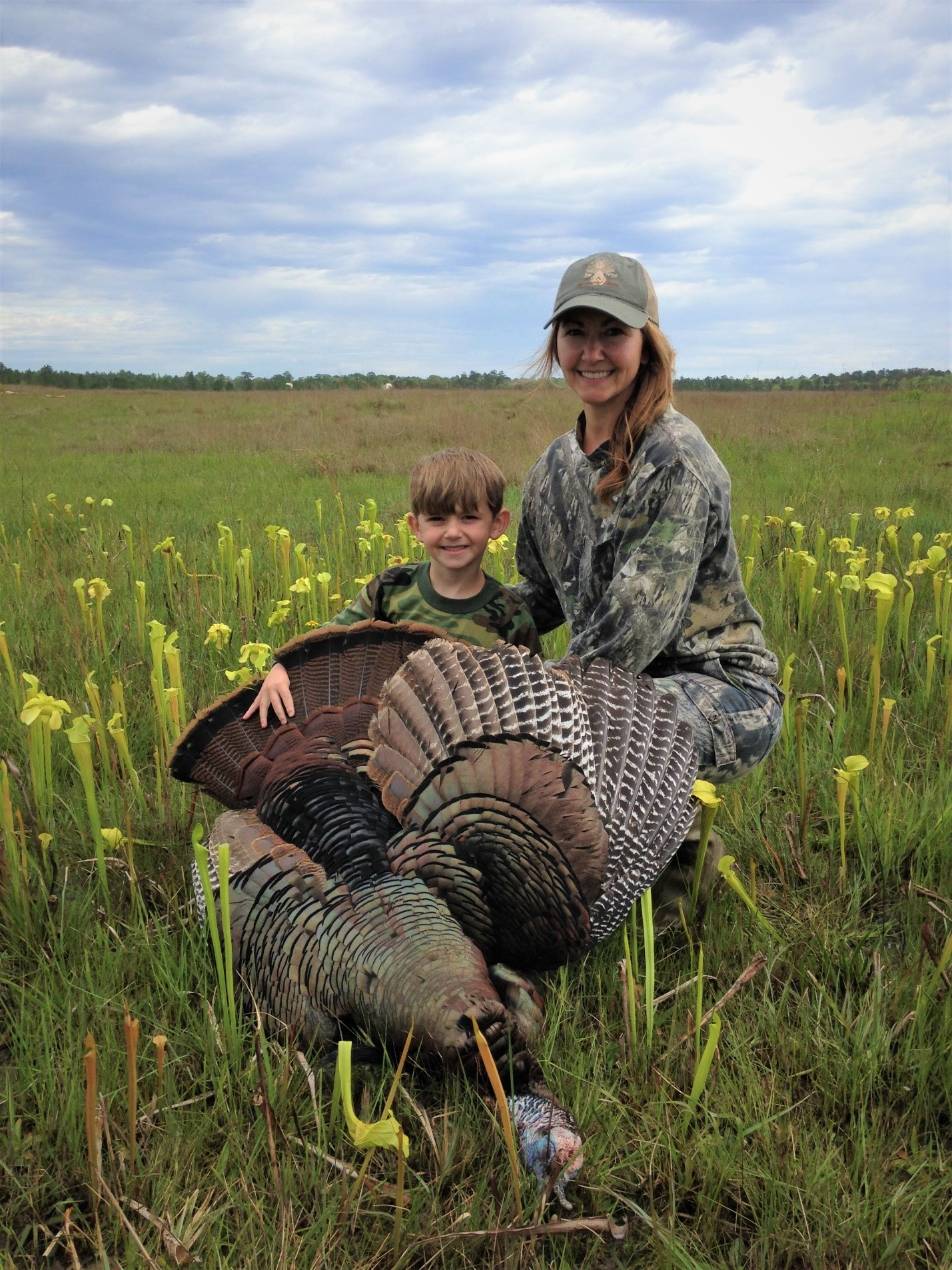 Image of mother and son (Pardue Family) with a turkey hunted on the Kisatchie National Forest.