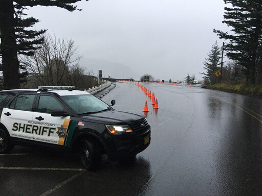 A police car and a line of orange cones on the historic highway marking a temporary closure.