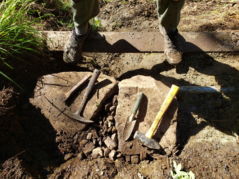 Photo of the feet with boots on with tools nearby