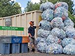 A man stands next to a tower of aluminum cans stacked in trash bags at a recycling center.