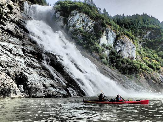 kayakers in front of an imposing cliff
