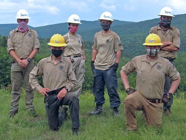 2020 ACC crew poses for a photo on a mountain vista. They are all  wearing protective cloth masks.