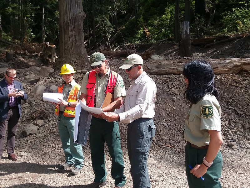 Forest Service workers stand on site in a semi circle and a few look at some plans and discuss.