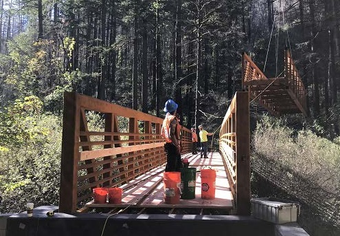 Image of a person standing near a trail bridge as a section is lowereed by helicopter.